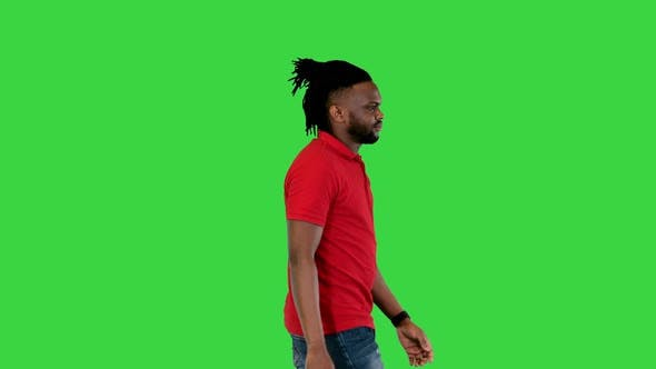 Young African American Man Walks and Takes a Look at His Watch on a Green Screen Chroma Key