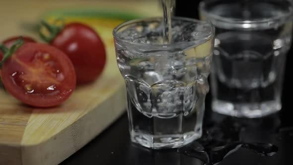 Thumbnail for Pour Alcohol Drink Vodka From a Bottle in Shot Glass. Surface with Snacks