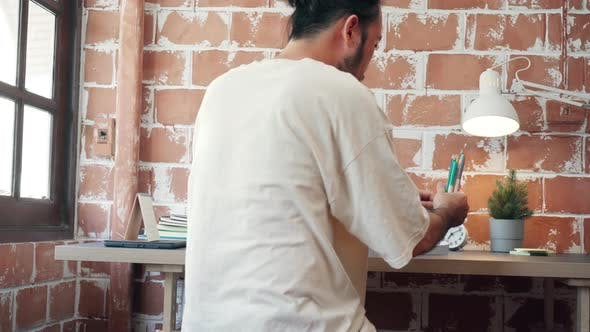 Asia guy with beard start working on laptop at his desk in living room at house in the morning.