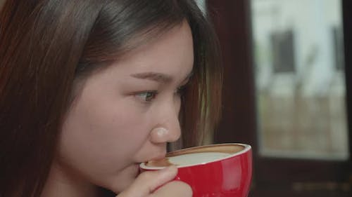 Asian Woman Holding And Drinking Hot Coffee In Cafe