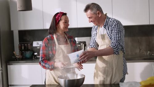 The Couple Sifting Flour to Make Bread in Kitchen