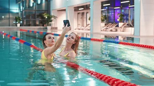 Young Females in the Swimming Pool Two Beautiful Girls in Yellow Swimsuits Take a Selfie on a