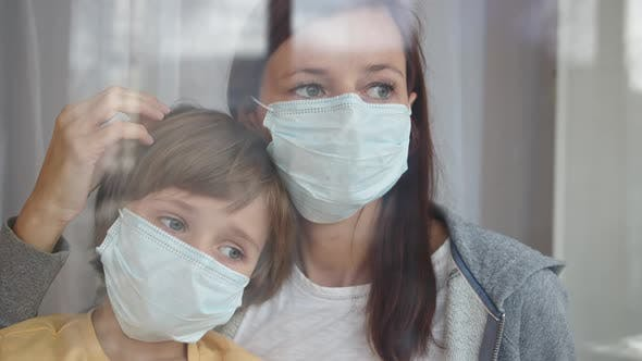 Family in Protective Masks Quarantined at Home