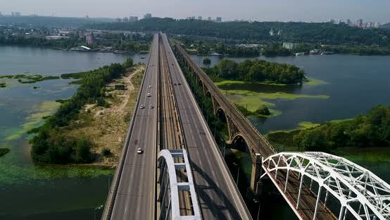 Aerial top view of automobile and railroad Darnitsky bridge across Dnieper river from above