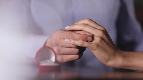 Marriage Proposal. Closeup Man Wearing Ring On Woman's Hand