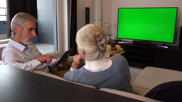 Thumbnail for Elderly Couple Sits on A Couch in A Living Room, Watches TV with A Green Screen and Work on Tablet