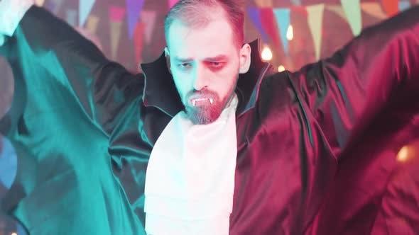 Thumbnail for Junger Mann verkleidet als Ghoul oder Vampir macht lustige Tanzbewegungen auf einer Halloween-Party