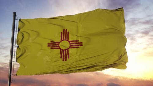 Flag of New Mexico Waving in the Wind Against Deep Beautiful Sky at Sunset
