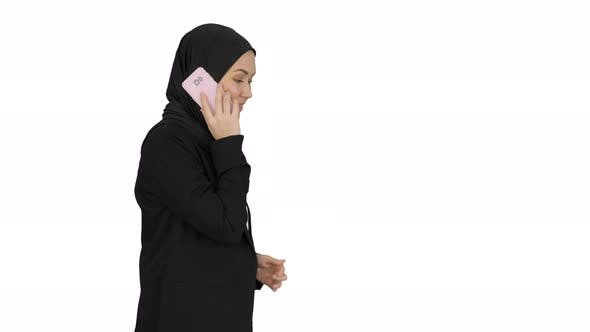 Attractive Modern Muslim Woman Walking and Talking on Cell Phone on White Background
