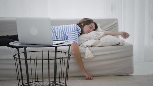 Tired woman sleeping in front of laptop