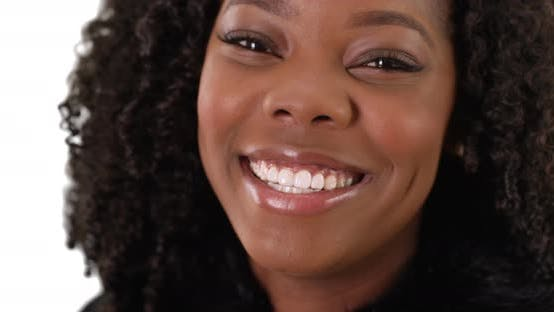 Thumbnail for Close up of beautiful African American female laughing at camera in studio