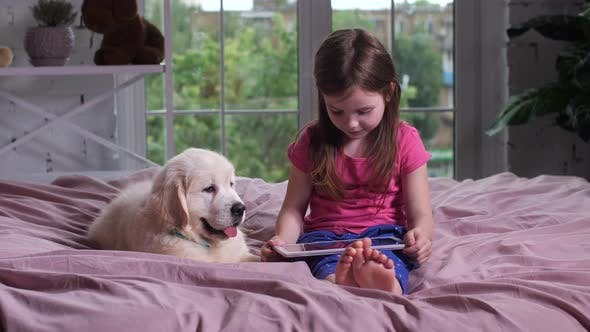 Thumbnail for Child Watching Video with Puppy on Bed