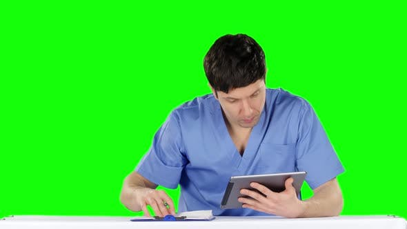 Thumbnail for Angry Doctor Using a Tablet and Makes Records. Green Screen