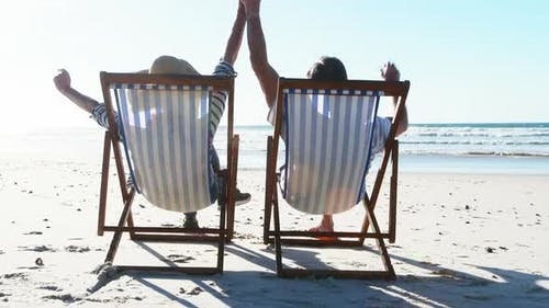 Senior couple relaxing on sunlounger at beach
