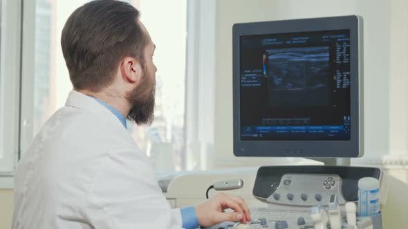 Thumbnail for Male Doctor Examining Results of Ultrasound Scanning of a Patient