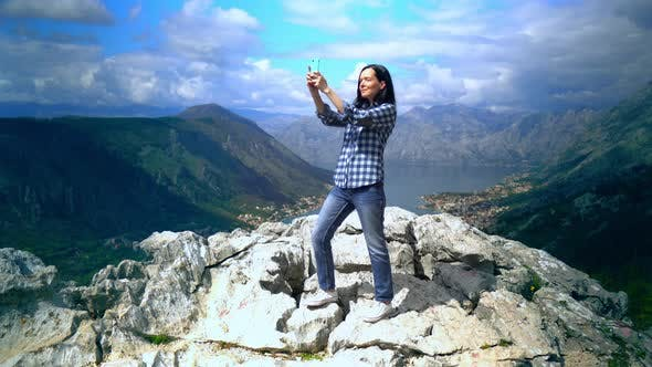 Thumbnail for Woman Standing on Top of Mountain with Smartphone and Taking Photo