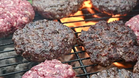 Cover Image for Cooking beef burgers on barbecue flame grill