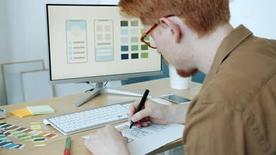Creative Specialist Choosing Colors for Mobile Phone Apps Coloring Pictures Looking at Computer
