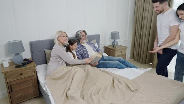 Grandparents Reading Book for Granddaughter While Relaxing Together in Bedroom