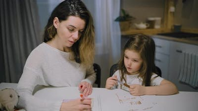 A Mother and a Small Daughter Draw Drawings on Paper in the Kitchen with Markers