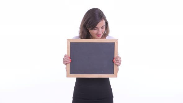 Thumbnail for Happy Beautiful Businesswoman Holding Blackboard and Looking Surprised