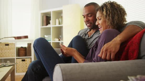 Thumbnail for Black couple using smartphone together on couch