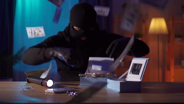 Funny Robber in a Balaclava Finds Jewelry on the Table and Tries Them on Himself