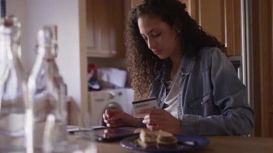Thumbnail for Attractive mixed ethnic woman making online payment with a tablet