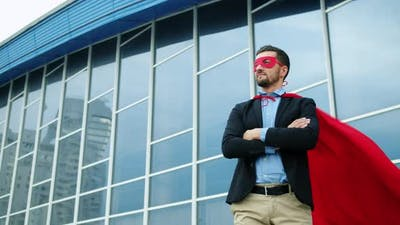 Portrait of Handsome Businessman in Suit Wearing Superman Costume Outdoors