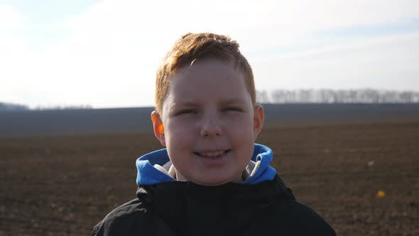Portrait of Funny Ginger Boy with Freckles Looks Into Camera Against the Blurred Background of