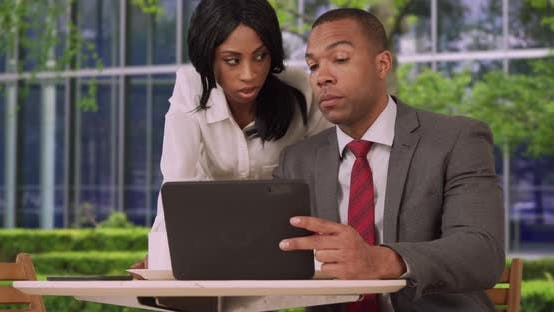 Thumbnail for Two aspiring African business associates check stocks on tablet