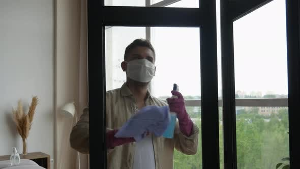 Thumbnail for Home window cleaning disinfection. Man in a medical mask cleans windows during quarantine.