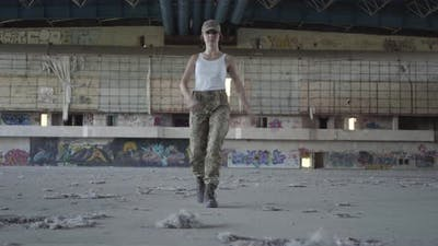 Attractive Young Woman in Military Uniform Marching on Concrete Floor in Dusty Dirty Abandoned Place