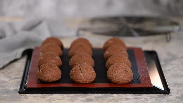 Freshly Baked Chocolate Profiteroles on Baking Sheet