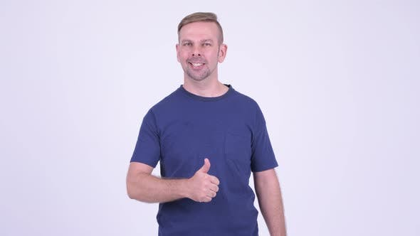 Cover Image for Portrait of Happy Blonde Man Giving Thumbs Up