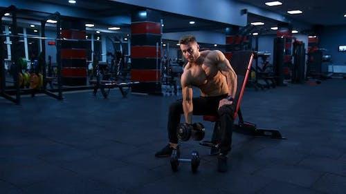 Bodybuilder trainieren mit Kurzhantel. Junger muskulöser Mann macht harte Übungen mit Hanteln