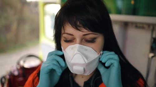 Female Emergency Doctor Takes Off Medical Face Mask Inside an Emergency Vehicle