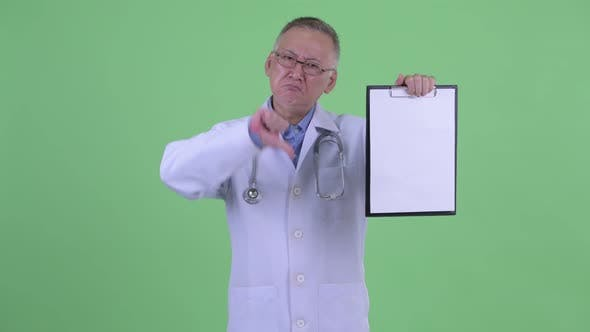 Thumbnail for Stressed Mature Japanese Man Doctor Showing Clipboard and Giving Thumbs Down