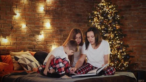 Mom Reads Bedtime Story To Children Indoors