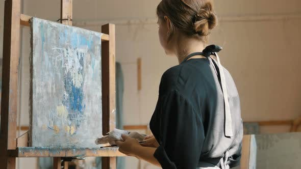 Artist with Hair Bun Applies Paint on Canvas Drawing Picture