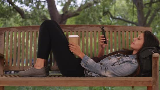 Cover Image for Caucasian millennial woman lying down on park bench and scrolling through phone