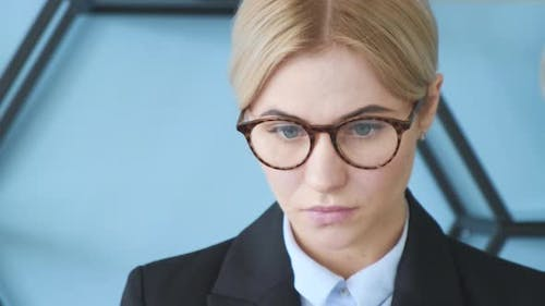 Confident face in glasses of business girl posing at office. Medium close up shot on 4k