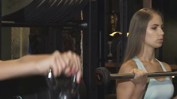 Cover Image for Beautiful Sportswoman Exercising with a Barbell at the Gym
