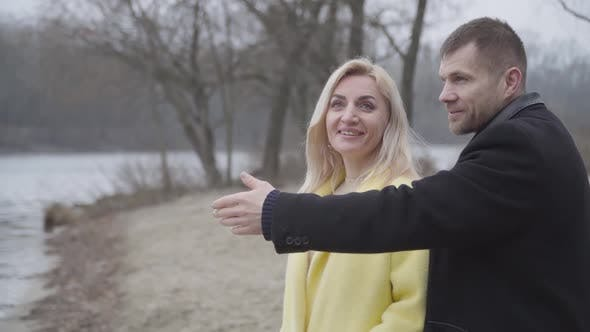 Thumbnail for Positive Caucasian Man Opening Eyes of Blond Smiling Woman on Riverbank and Kissing Sweetheart