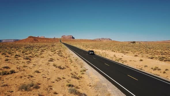 Thumbnail for Drone Follows Silver Car Driving Along Amazing American Desert Landscape, Empty Highway Road