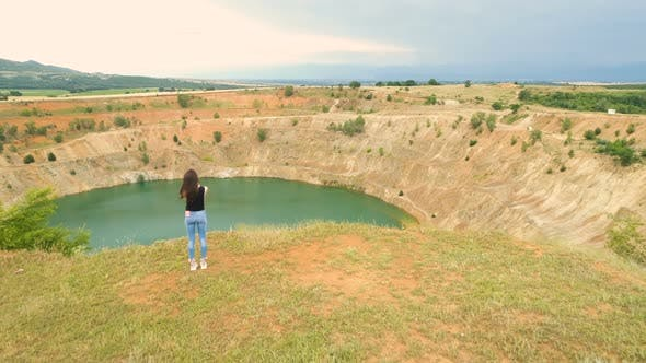 Lonely Woman Taking Photos of Open Mine Pit Filled with Blue Water in Tsar Asen Village, Bulgaria