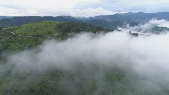 Thumbnail for Aerial View of Dense White Mist Covering Green Hills and Mountain Tops