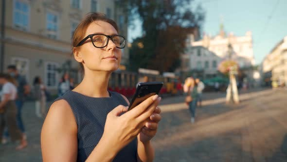 Woman Standing on an Old Street, Using Smartphone and Looking Around