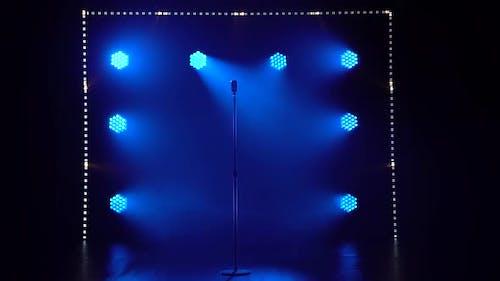 Silhouette eines Konzert-Vintage-Mikrofons, das in einem leeren dunklen Studio mit Smoke steht. Ein Blau