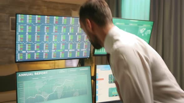 Thumbnail for Broker Arriving in Home Office and Checking the Stock Market